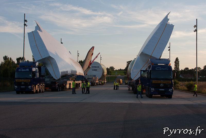 Sur l'aire de stationnement de l'Isle Jourdain (32) le convoi prépare son départ vers Cornebarrieu (31), à gauche : aile gauche, empennage horizontal, et fuselage central. A droite aile droite