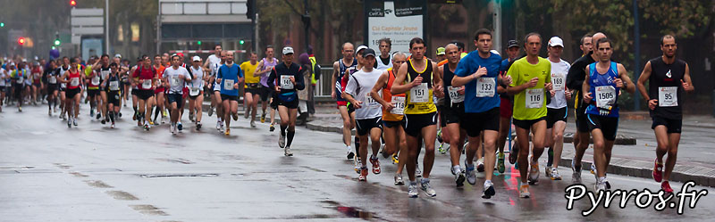 Panoramique : Sous la pluie d'automne, se deroule, le quatrième marathon du Grand Toulouse, Kilometres 3 : Compans Caffarelli. Le flot des coureurs s'étend du pont des Catalans à la place Arnaud Bernard