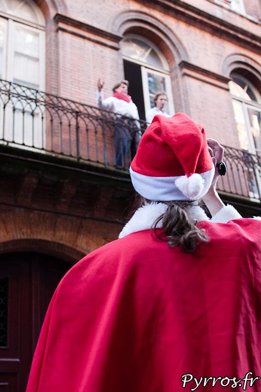 Depuis leur balcon deux personnes chantent des chants de Noël SantaCon Toulouse
