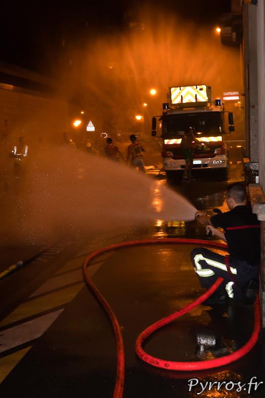 Appuyé sur le mur pour plus de stabilité, le sapeur pompier arrose les randonneurs