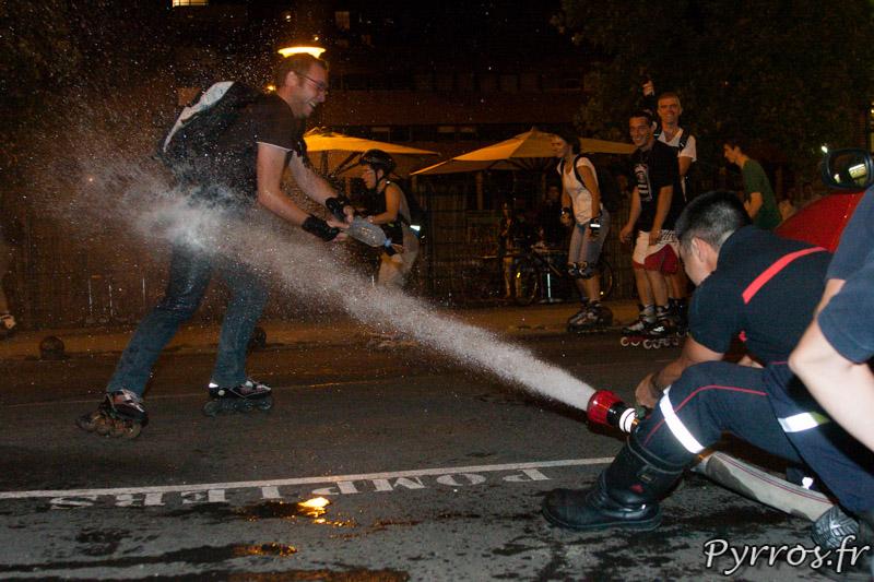 Cachés derrière une voiture les pompiers ripostent face aux attaques de certains randonneurs, Roulez Rose organise avec l'aide des pompiers de Toulouse la rando roller pistolets à eau