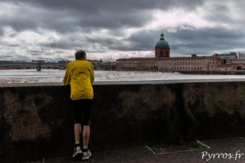 Sur la digue du Bazacle un joggeur fait une pause et devient specateur de la Garonne