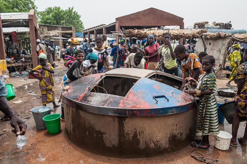 Au marché, les enfants se rassemblent autour du puits par Christophe Gressin