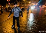 Avec une moustache les patineurs s'élancent avec le sourire sur un chaussée humide