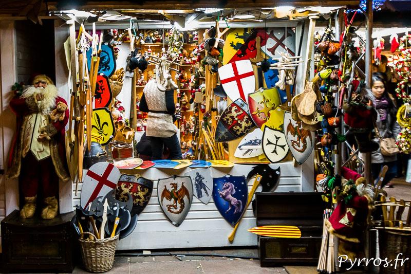 Un chalet propose au milieu des figurines de Noël des boucliers et autres armes du Moyen Age