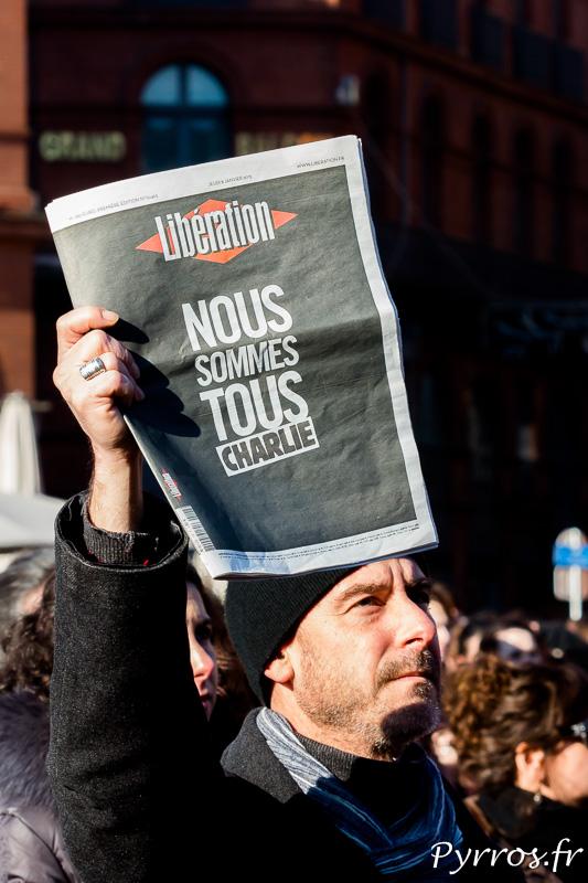 Certains toulousains montrent la couverture d'un journal rendant hommage à Charlie Hebdo