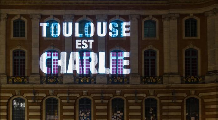 """La façade gauche du Capitole sur laquelle est projetée le message """"Toulouse est Charlie"""". Au pied de la façcade les toulousains ont déposés des bougies et ont accrochées des messages"""
