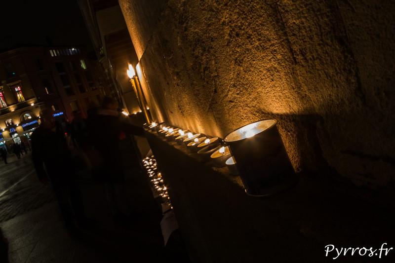 Un alignement de bougies déposées sur le mur du Capitole