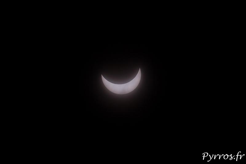 Au milieu de nuages on peut voir le croissant de soleil lors de l'éclipse du 20 Mars 2015