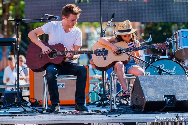 Un prof de guitare accompagne son élève qui joue un morceau