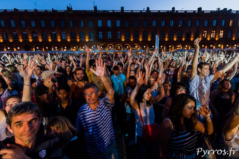 Le public a les mains en l'air sur la place du Capitole