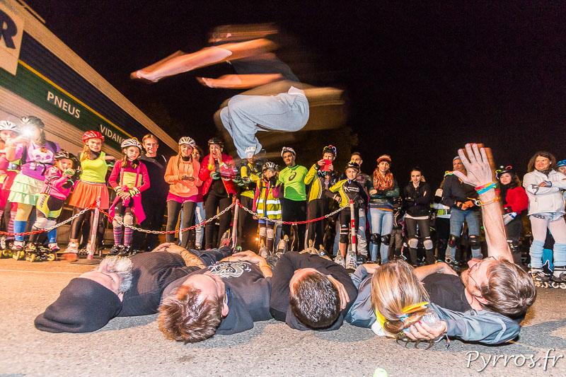 Toujours impressionnant, ce patineur saute par dessus 5 personnes volontaires allongés sur le sol