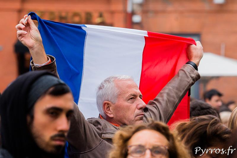 Pendant la minute de silence un homme brandit un drapeau tricolor