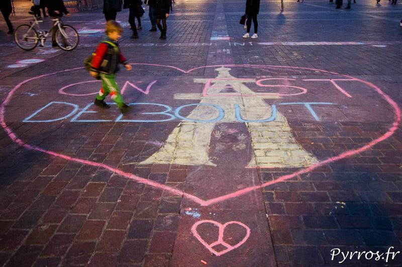 """Un enfant marche dans un cœur qui entoure le slogan """"On est debout"""""""