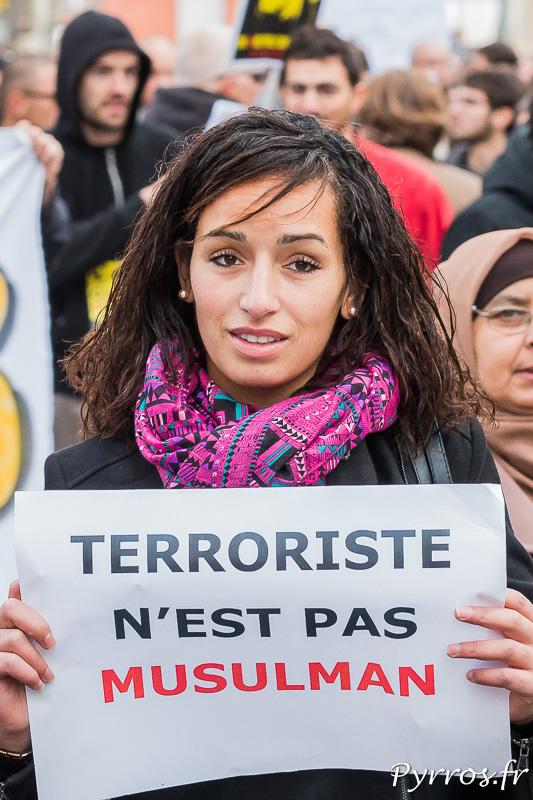 """Une jeune femme tient une affiche """"Terroriste n'est pas Musulman"""""""