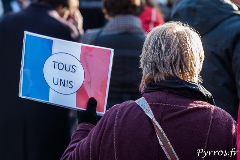 """""""Tous unis"""" inscrit sur une affiche tricolore"""