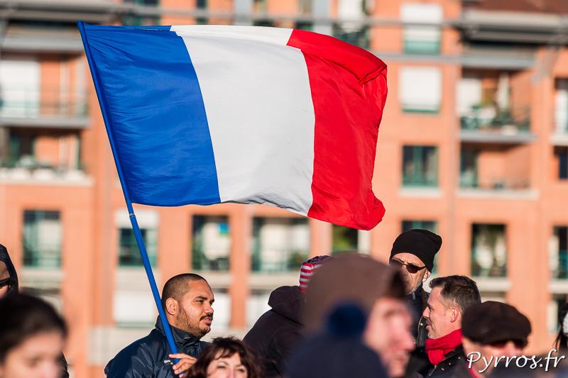 Une homme brandi le drapeau tricolore