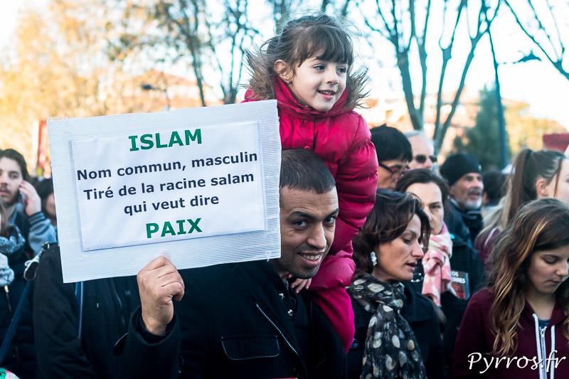 """Un père de famille montre une pancarte qui explique la racine du mot """"Islam""""Un père de famille montre une pancarte qui explique la racine du mot """"Islam"""""""