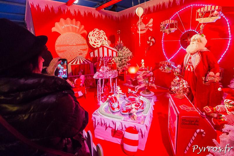 Certains visiteurs visitent le Père Noël au Pays des Friandises avec le smartphone à la main