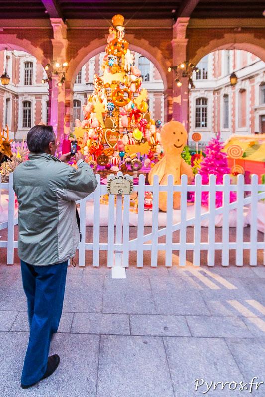 Un homme prend en photo le Jardin des friandises du Père Noël installé dans la cour du Capitole