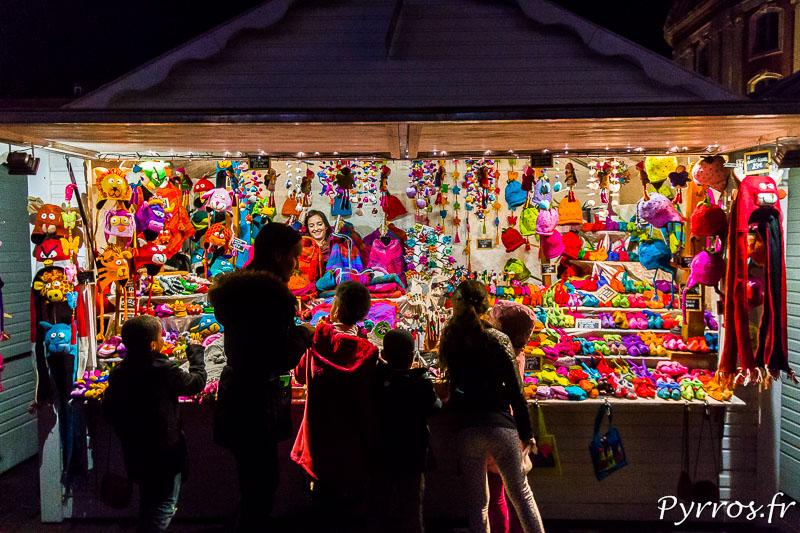 Une famille observe les produits vendus dans un chalet du Marché de Noël de Toulouse