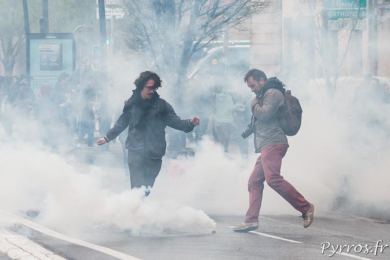 Des manifestants tentent de repousser les lacrymogènes