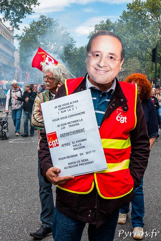Un manifestant de la CGT porte un masque du président de la république François Hollande