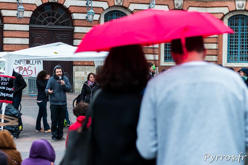Certains s'abritent sous un parapluie le temps d'une rapide averse pour écouter les participants