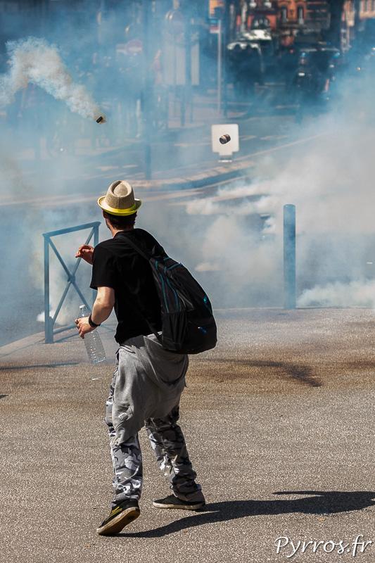 Un manifestant surveille les grenades lacrymogènes lancées par les force de l'ordre en fin de manifestation