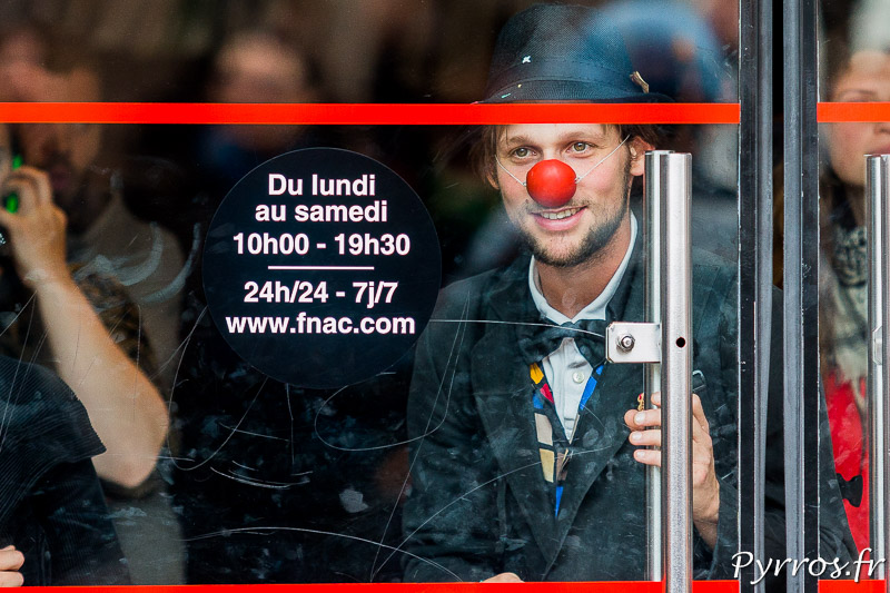Derière la vitre de la FNAC un manifestant fait le clown durant l'Opération Champagne
