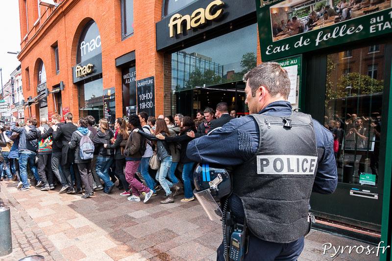 Les manifestants sortent de la FNAC dans une joyeuse farandole sous le regard d'un policier