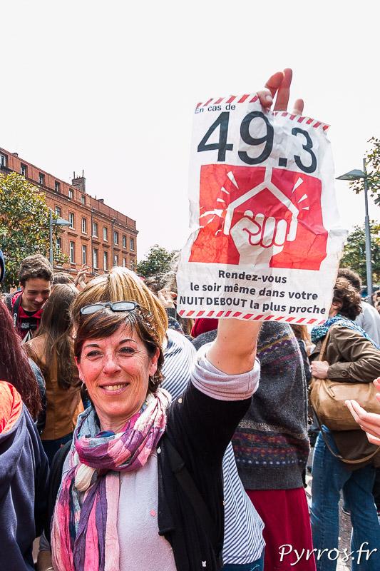 Une manifestante sort de la FNAC en tendant un trac contre l'utilisation du 49.3