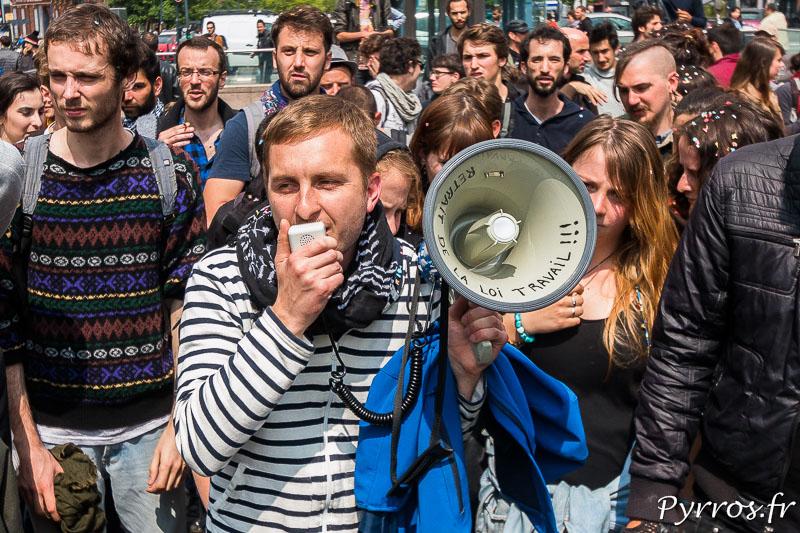"""Un des organisateurs de l'Opération Champagne dans la FNAC parle dans le mégaphone sur lequel on peut lire """"Retrait de la Loi Travail !!!"""""""