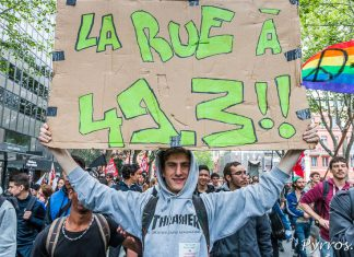 Sur une grande pancarte une manifestant affiche son opposition à l'utilisation du 49.3