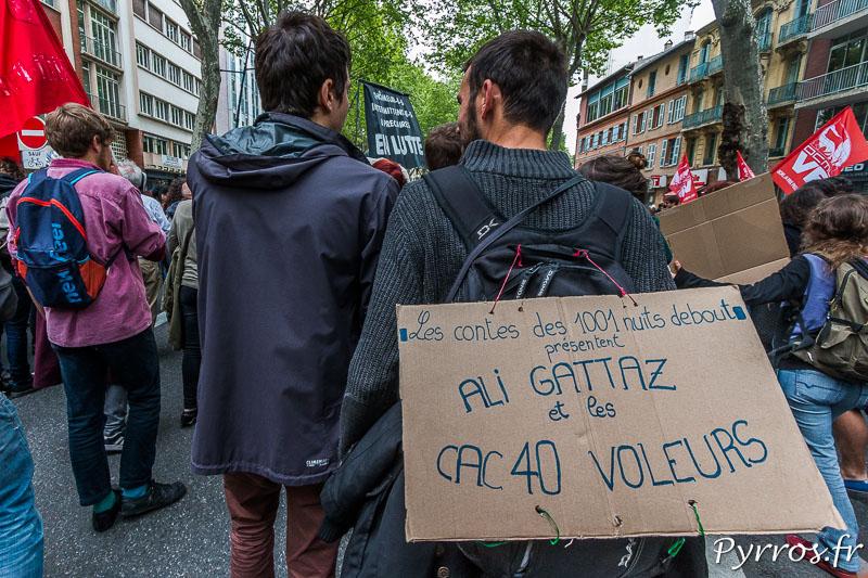 Sur son sac un manifestant critique avec humour l'attitude du MEDEF et des entrerprises du CAC40