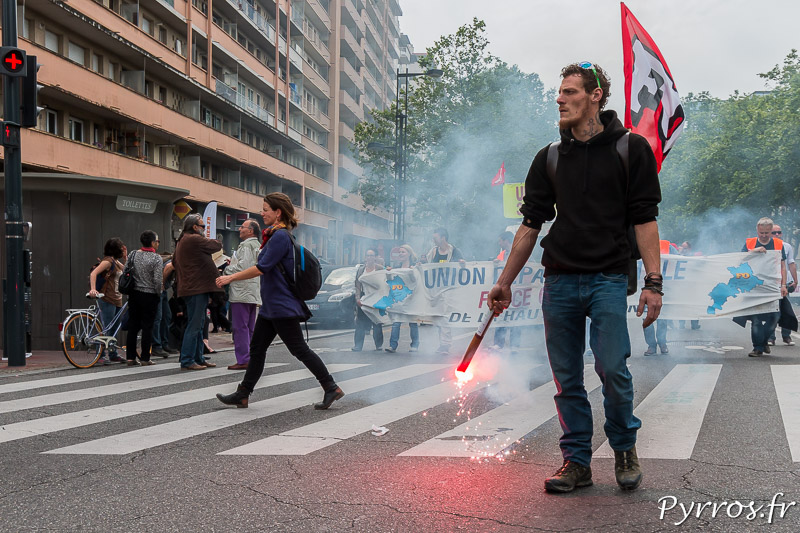 A Toulouse un manifestant porte un fumigène devant une banderoleA Toulouse un manifestant porte un fumigène devant une banderole