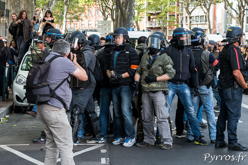 Un photographe prend une photo des forces de l'ordre protègent leurs collègues en train d'interpeller un manifestant