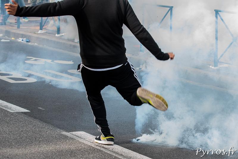 Un manifestant tente de renvoyer un palet de lacrymogène en direction des forces de l'ordre