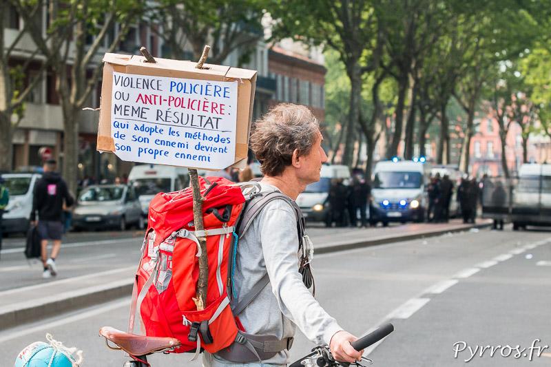 Sur la pancarte de ce manifestant pacifiste on peut lire une critique des violence policière et anti-policière