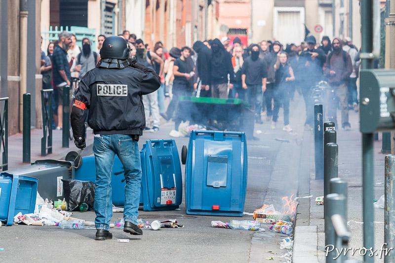 Un policier observe les manifestants dont certains cagoulés ou masqués qui ont tenté de se barricader derrière un amoncelement de poubelle