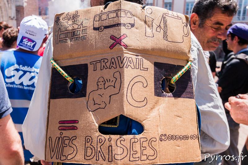 Sur le sac d'un manifestant est affiché un rébus
