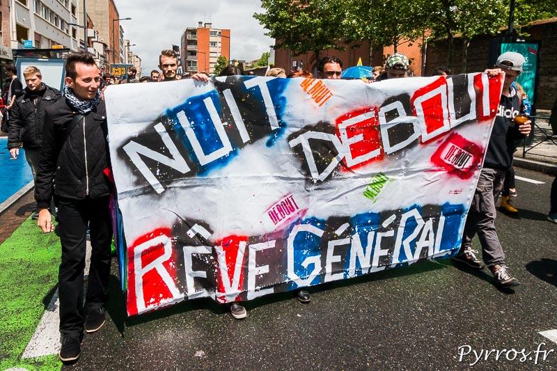 Des membres de Nuit Debout défilent derrière une banderole, avant de se faire interpeller par un passant qui les traite de faignant