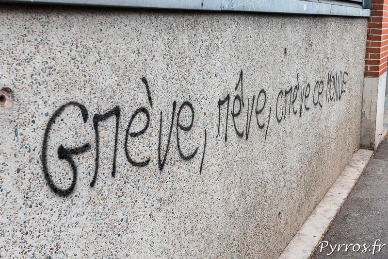 """Le mur d'une banque a été tagué par un manifestant il a inscrit """"Grève, rêve, crève ce Monde"""""""