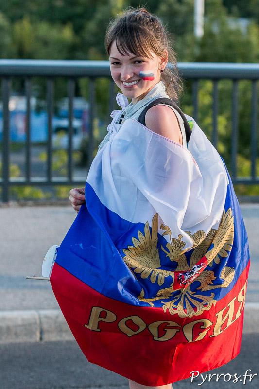 Une supprotrice russe se rend au stadium habillée d'un drapeau de la Russie