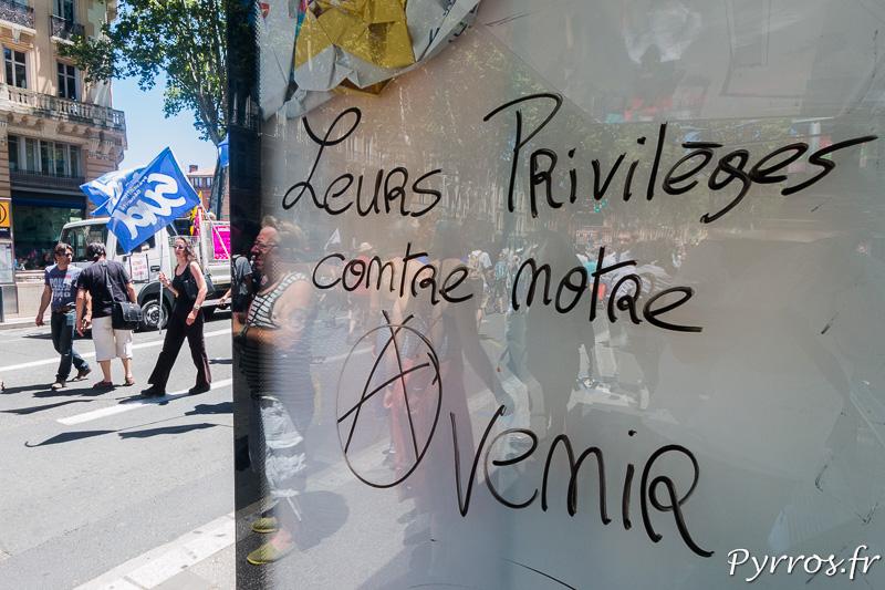 """Sur un panneau publicitaire a été écrit """"Leurs privilèges contre notre avenir"""" avec le a reprenant le la graphie de celui des anarchistes"""