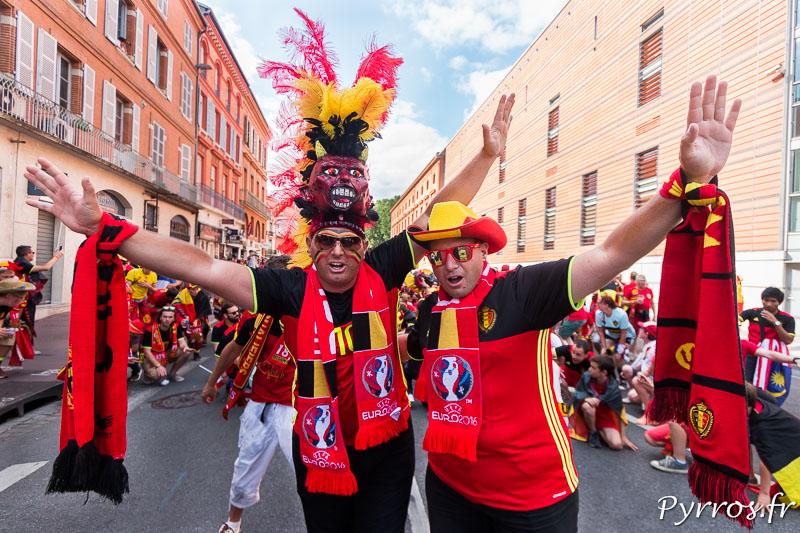 2 supporters belges posent ensembles devant le cortège de supporters