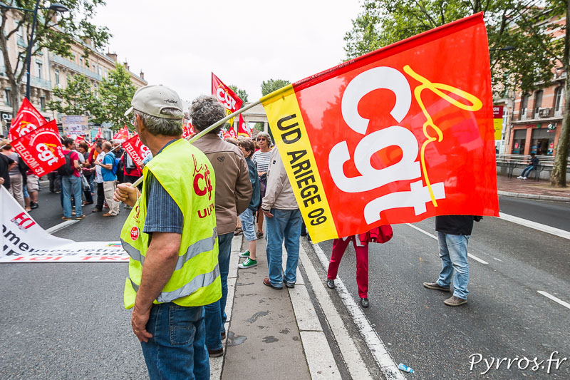 Un membre de la CGT avec un drapeau observe la manifestation se mettre en place