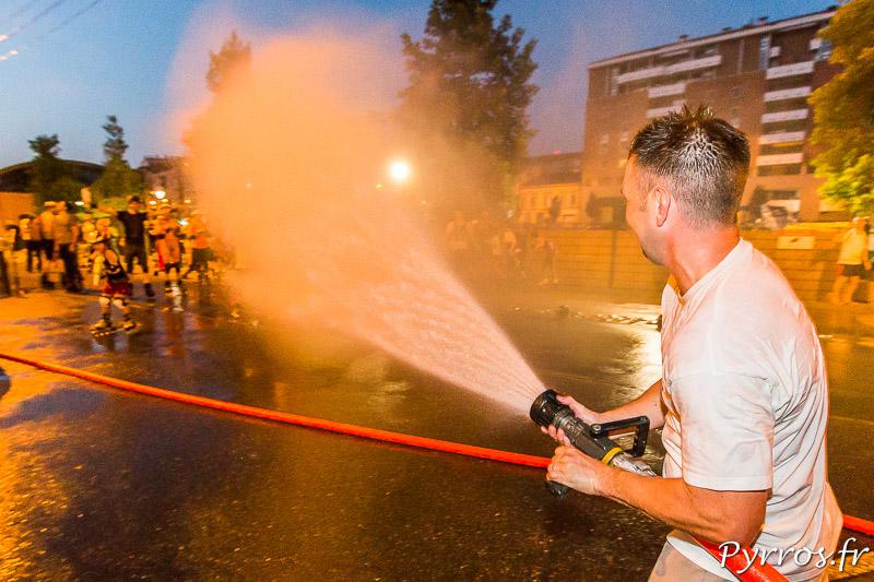 Avec une lance à incendie au débit important un pompier noie les patineurs sous des litres d'eau
