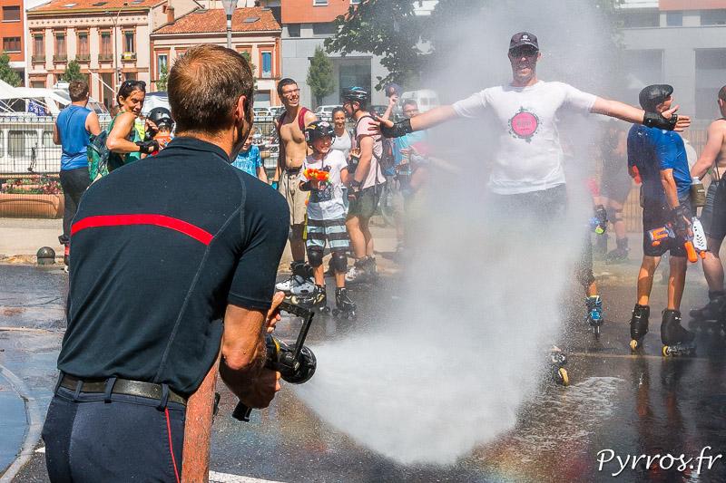 Un pompier de la caserne Lougnon arrose un patineur lors de la randonnée roller pistolet à eau