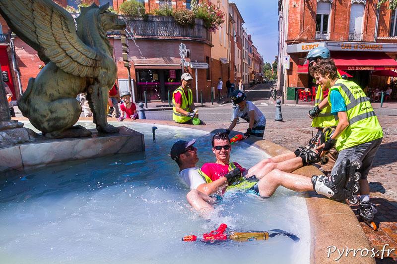 Un staffeurs est poussé dans la fontaine rafraichissante, il entraine dans sa chute un patineur